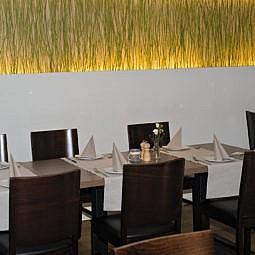 Restaurant Tisch, Stühle und beleuchtete Wand